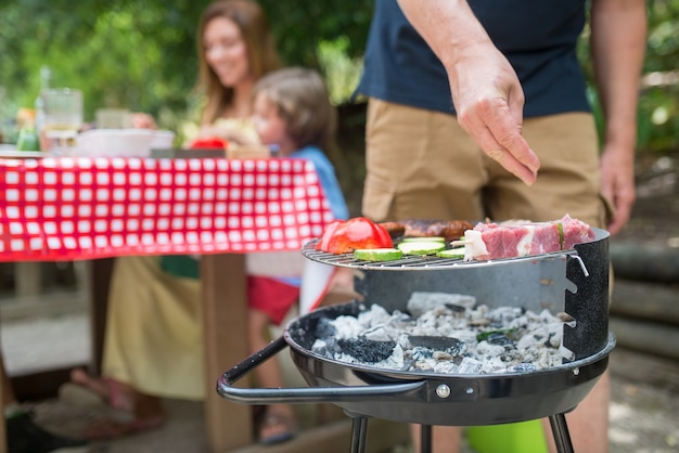Primo piano del padre che cucina barbecue. metà uomo adulto in piedi alla griglia del barbecue, cucinando carne fresca. madre e figli seduti a tavola insieme