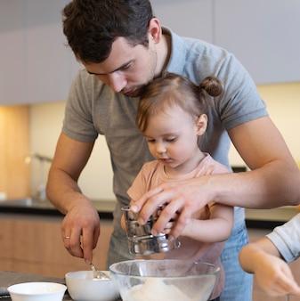 Макро отец помогает ребенку с мукой
