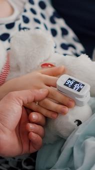 Primo piano del padre che tiene le mani della figlia malata dopo aver subito un intervento chirurgico contro l'infezione da malattia durante l'esame di recupero. ragazza ricoverata che riposa a letto con un ossimetro medicinale sul dito