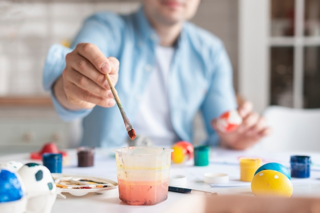 Close-up father painting easter eggs