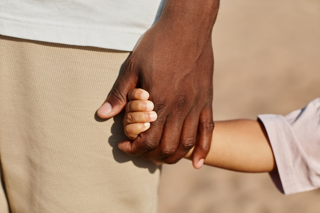 Close up of father and son holding hands while enjoying walk on beach in sunlight copy space