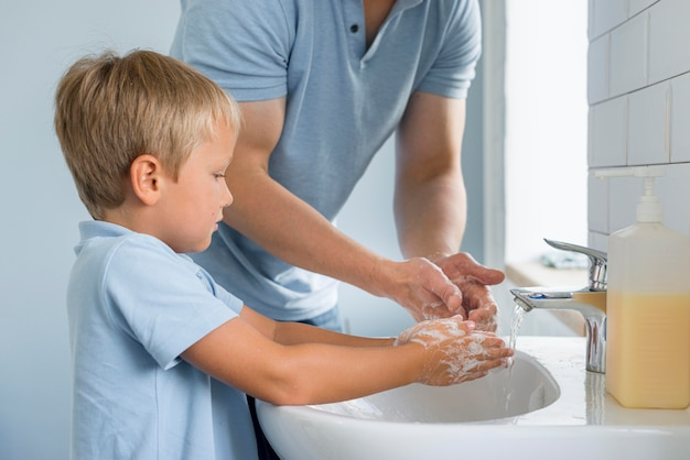 Close-up father teaching son how to wash hands