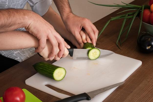 Крупным планом отец учит сына нарезать овощи