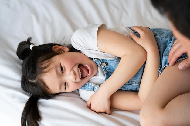 Close up father tickling girl
