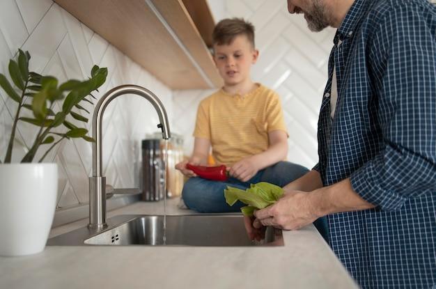Chiuda sulla verdura di lavaggio del padre