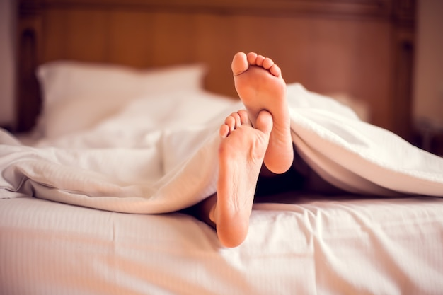 Close up of feet in a bed under blanket. people and lifestyle concept
