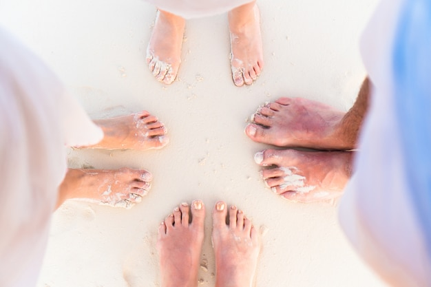 Close-up of the feet of family on the white sandy beach