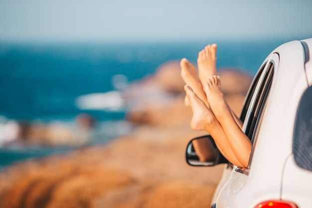 Close up of feet from car window on vacation background the sea