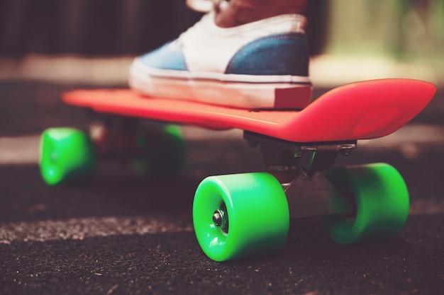 Close up of feet of girl sneakers rides on orange penny skateboard on asphalt