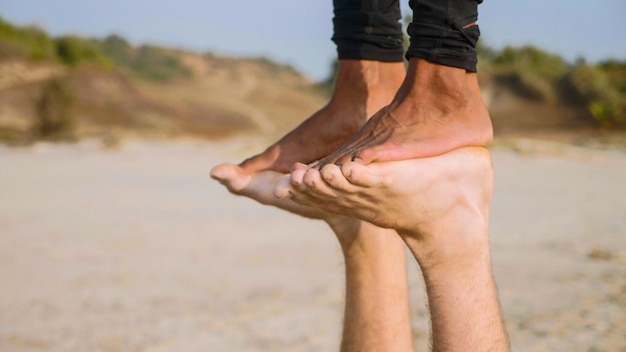 砂浜で一緒にパートナーとアクロヨガを練習する若いスポーティなカップルのクローズアップの足