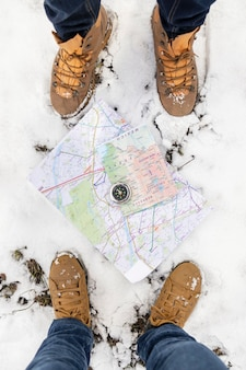 Close up feet with maps and snow
