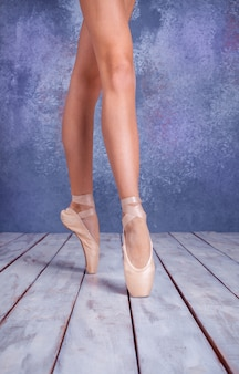 The close-up feet of  young ballerina in pointe shoes against the background of the wooden floor