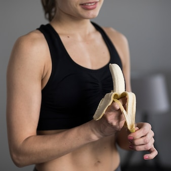 Close-up of female in activewear peeling banana