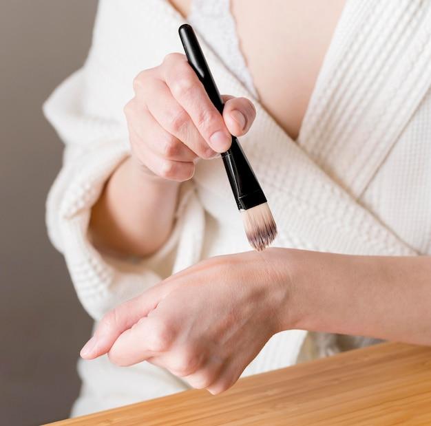 Close-up female applying foundation