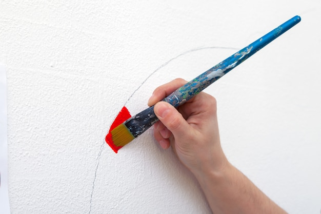 Close-up of a female artist draws on a wall with a large wooden tassel in red