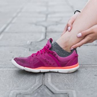 Close-up of female athlete having ankle pain on concrete pavement