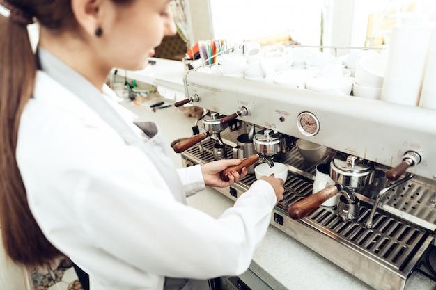 Close up of female barista preparing coffee