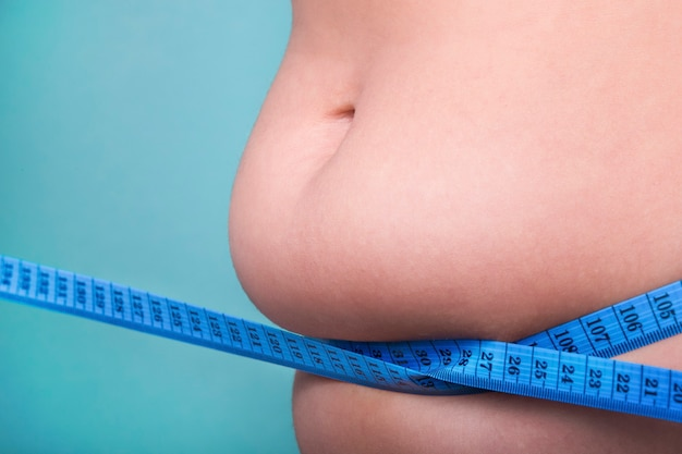 Close-up female belly with overweight wrapped with a measuring tape, the concept of proper nutrition and diet for weight loss