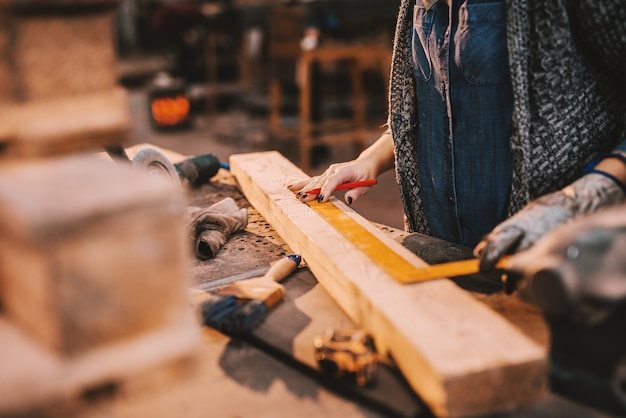 Close up of female carpenter working in workshop. female doing male's work concept.