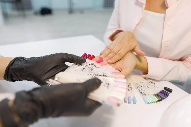 Close-up of female choosing nail-polish color for her nails