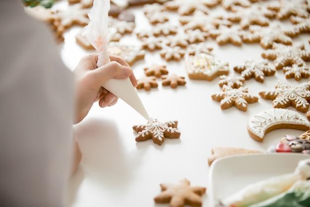 Primo piano di mani femminili di confettero ghiacciando le stelle di pan di zenzero