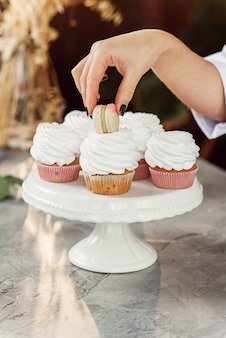 Close up female confectioner's hands put a fresh macaron on top of the cupcake with cream.