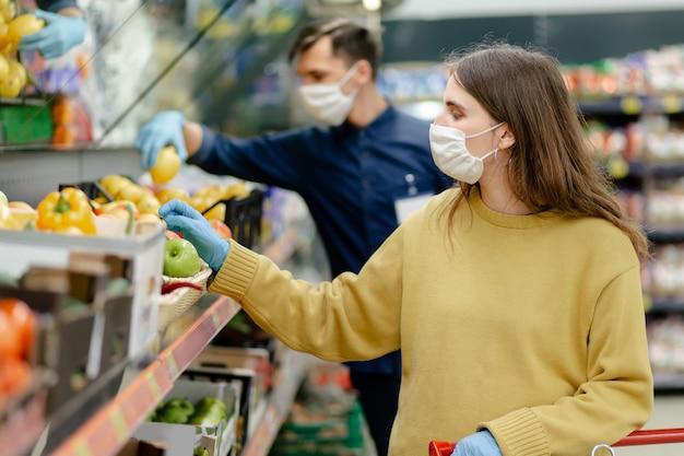 확대. 상점에서 과일을 선택하는 보호 장갑에 여성 고객. 건강 보호의 개념.