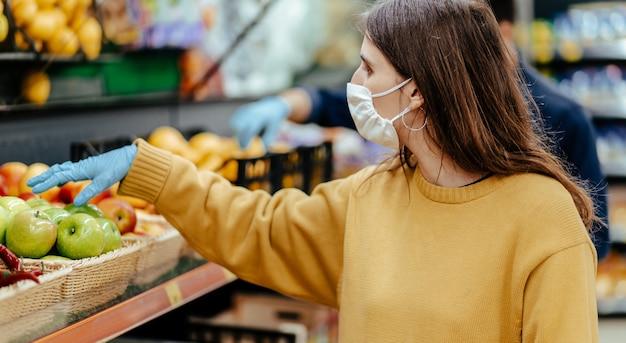 閉じる。店で果物を選ぶ保護手袋の女性の顧客。
