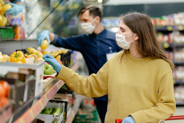 Close up. female customer in protective gloves choosing fruit in the store. concept of health protection.