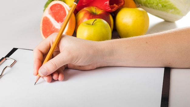 Close-up of a female dietician's hand writing on clipboard with pencil