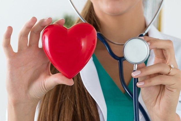 Close-up of female doctor hands holding read heart and stethoscope head. healthcare and medical concept