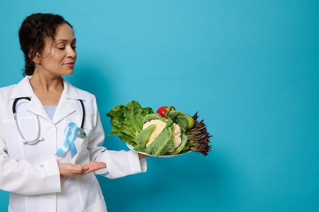 Close-up of female doctor nutritionist in white medical gown with blue awareness ribbon points on plate with healthy raw vegan eating. world diabetes day concept on colored background with copy space