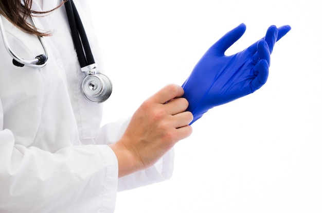 Close-up of a female doctor wearing the blue surgical glove against white backdrop