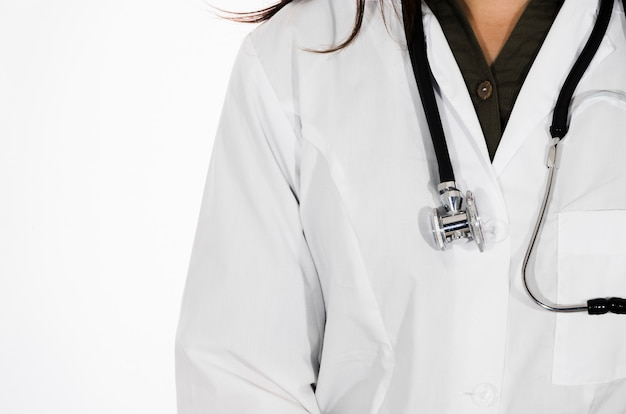 Close-up of female doctor with stethoscope around her neck isolated on white backdrop