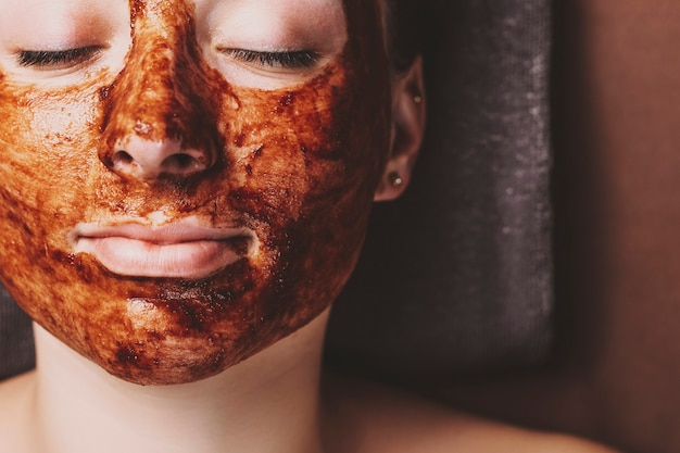 Close up female face leaning on a spa bed with closed eyes with anti acne chocolate mask in spa center.