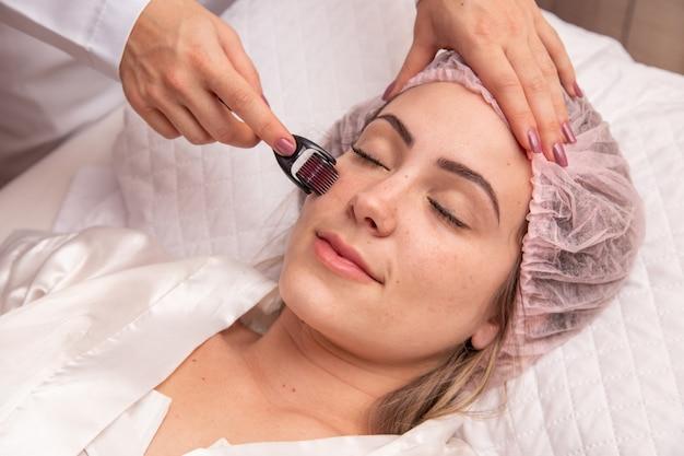 メソセラピー手順、自宅やサロンでのスキンケアのためのダーマローラー付きのクローズアップ女性の顔。マイクロニードル付きメソローラー。