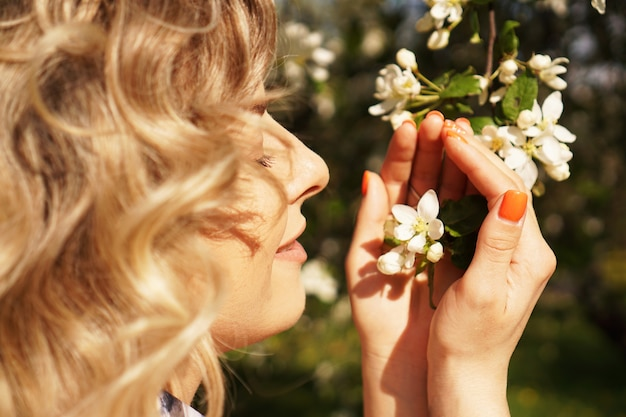 Close-up of female face, woman sniffing white flowers blooming apple tree in garden