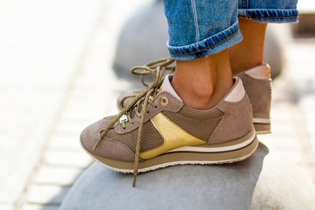 Close-up of female feet in beige sneakers. woman in fashionable shoes outdoors