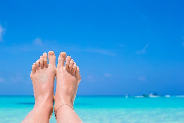 Close up of female feet on white sandy beach