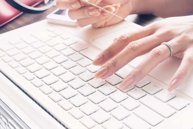 Close up of female fingers using laptop and credit card, working woman and online shopping concept, selective focus