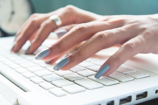 Close up of female fingers using laptop, working woman and online shopping concept, selective focus