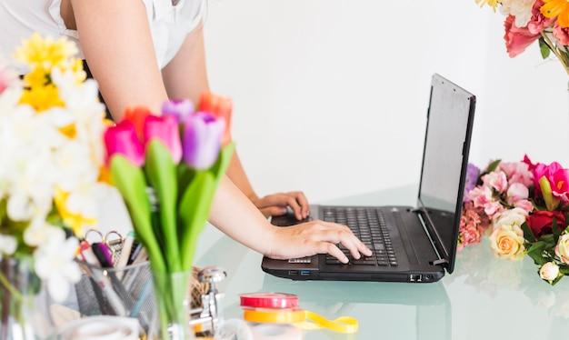Close-up of a female florist hand working on laptop