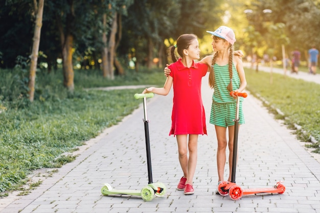 Close-up of female friends standing with their scooters on walkway