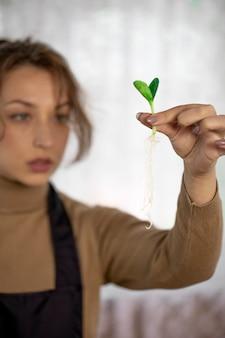 Крупным планом женщина-садовник, держащая овощи микрозелени