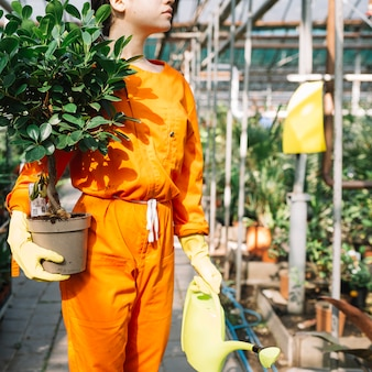Close-up of a female gardener in workwear holding potted plant and watering can