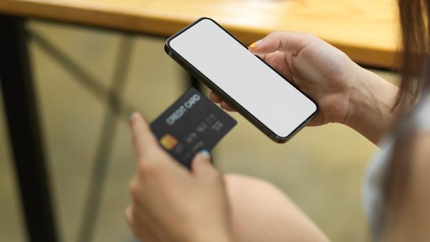 빈 화면 온라인 쇼핑으로 여성의 손을 잡고 신용 카드와 스마트폰을 닫습니다