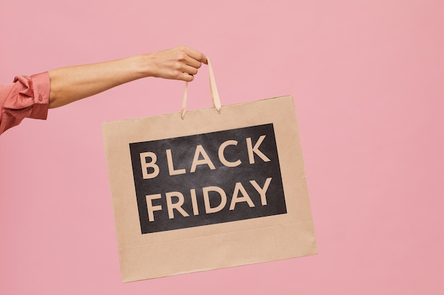 Close-up of female hand holding black friday shopping bag against the pink background