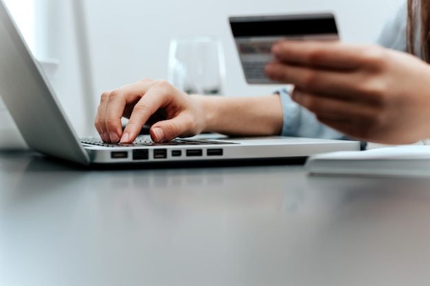 Close-up of female hand holding credit card and laptop making internet purchase.