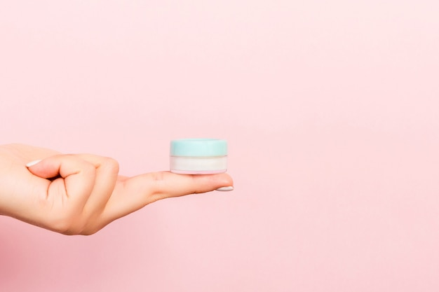 Close up of female hand holding a jar of cosmetics on pink background