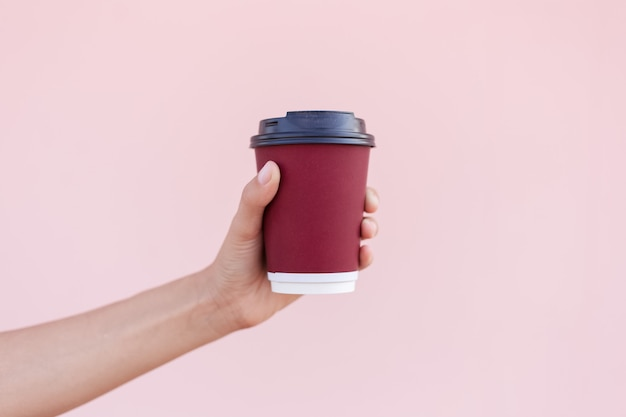 Close-up of female hand holding a paper coffee cup on the background of pastel pink color.